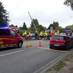 Räddningsmanskap på plats vid en trafikolycka där en bil kört in i en lyktstolpe.