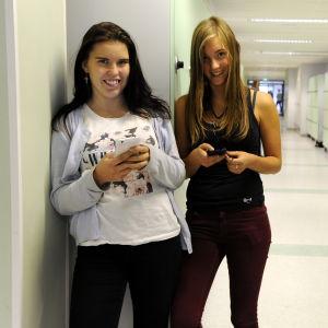 Linnéa Bäcklund och Cecilia Granlund, står med mobilerna i korridoren i högstadiet i petalax,