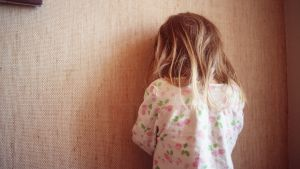 Barn som gömmer sig mot en vägg