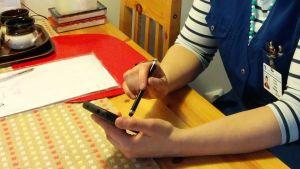 Hemvårdares händer vid ett köksbord. Antecknar saker på sin mobiltelefon.
