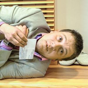 Eppu Salminen makaa lattialla harmaassa puvussa sarjassa Tahdon asia.