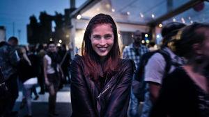 nuori nainen katsoo kohti ja hymyilee hämyisässä illassa, taustalla festariväkeä