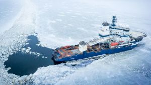 Valkoisella ja sinisellä maalattu jäänmurtaja murtaa jäätä merellä.