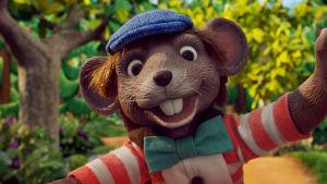 Närbild på dockmusen Klas Klättermus som ler och tittar rakt in i kameran.