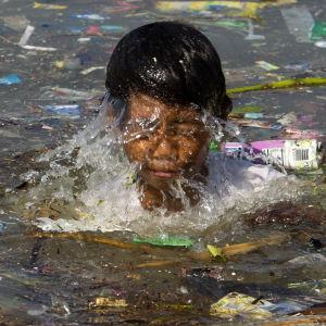 En filippinsk pojke simmar bland skräp i Manila. Önationen Filippinerna är extrakänslig för stigande havsnivåer.