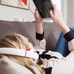 Tyttö makaa sohvalla, käyttää tablettia.