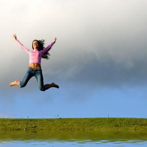 En flicka hoppar högt upp i luften.