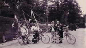 Kukkasin ja viirein koristeltuja polkupyöriä. Polkupyöräilijöitä 1900-luvun alussa.