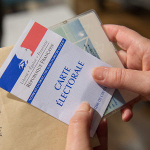 Händer håller i en fransk valsedel.