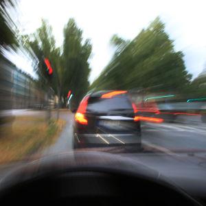 Suddig bild av en bil i trafiken.
