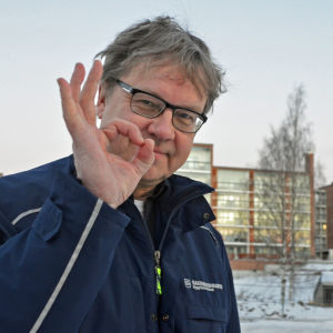 Pekka Sauri poserar med handen höjd i en OK-gest.
