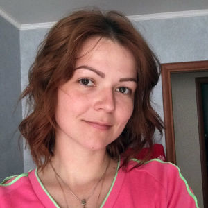 ung kvinna i ljusröd skjorta tittar in i kameran.