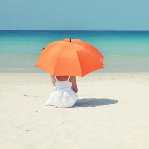 Kvinna sitter under ett parasoll på en sandstrand.