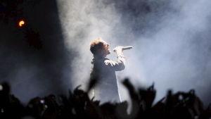 Bono som är sångare i U2 sjunger omgiven av fans på en rökig scen.
