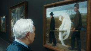 Gammal man står och ser på Hugo Simbergs målning Den sårade ängeln.
