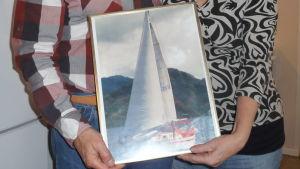 Bild på Anneli och Seppo sarekoski i deras kök i Ekenäs. Bilden fokuserar på en tavla av segelbåten Sampo.