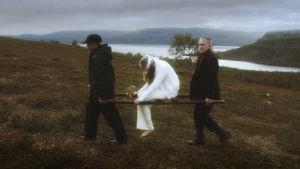 """Två gossar bär en bår där en sårad, vit ängel sitter. Fotot återskapar Hugo Simbergs målning """"Sårad ängel""""."""