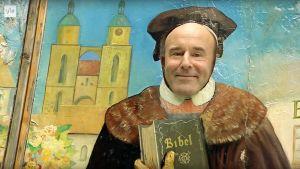 Mark Levengood tintamareskin takana, esittää Martti Lutheria