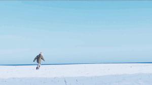 En barn springer på ett öppet fält täckt av snö.