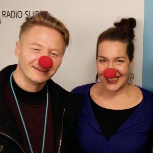Mikki Kauste, Tuuli Saksala ja Pekka Laine seisomassa Radio Suomen tunnuksen edessä, kasvoilla 'nenäpäivänenät'.
