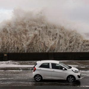 Stormen Eleanor slår upp en våg över en bil i Storbritannien.