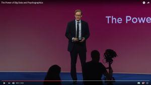 Skärmdump av en Youtubevideo där Alexander Nix håller föredrag i kostym och glasögon med tv-bågar.