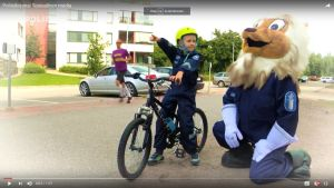 En pojke i poliskläder och polislejonet i ett videoklipp.