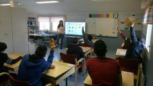 Elever på lektion i förgrund med lärare som pratar vid tavlan