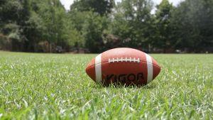 Amerikansk fotboll i gräset.