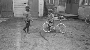 Lapset leikkivät pihalla. Kaksi lasta ja polkupyörä.
