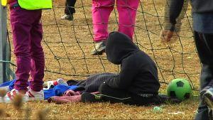 Barn som sitter bakom ett fotbollsmål.