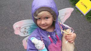 Tyttö, jolla on selässään keijusiivet ja kädessä leluja.