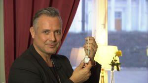 Marko Björs håller upp ett runt silversmycke.