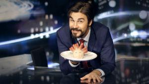 Noin viikon uutiset -ohjelman juontaja Jukka Lindström poseeraa makkarasiilin kanssa