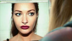 Elsa Rinne ser på en modebild med en kvinna med septum piercing.