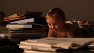 Vauva konttaa kirjapinojen keskellä