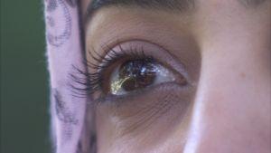Öga av ung arabisk kvinna med huvudduk