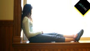 Nainen istuu ikkunalaudalla ja tuijottaa ulos.