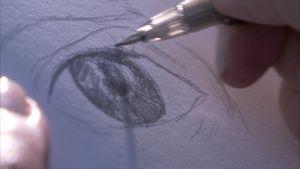 närbild av en blyertspenna som tecknar ett öga