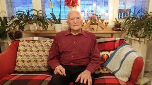 Krigsveteranen Levi Backholm sitter på sin soffa hemma i Sundom.