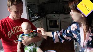 Lapsi miehen sylissä, nainen syöttää lasta.