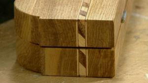 Detalj från ett brädspel av trä, dekorerat med intarsia av både mörka och ljusa träslag.
