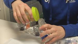 Idrottare häller urinprovet i testflaskorna vid ett dopningstest