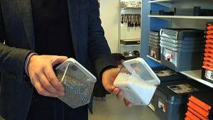 händer som håller burkar med plastmaterial
