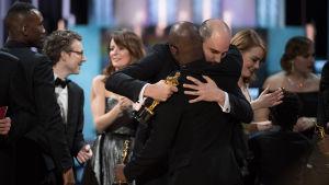 La La Land -elokuvan tuottaja Jordan Horowitz halaa Moonlight-elokuvan ohjaajaa Barry Jenkinsiä.