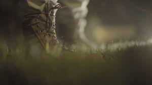 Nattlig bild av foten på en soldat som står på en gräsmatta.