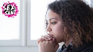 en ung kvinna som lutar sitt ansikte på sina händer och ser fundersam ut