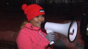 Arrangören Tanja Piha talar i megafon inför starten i ett motionslopp.