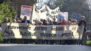 """Demonstranter med ett lakan med texten """"Fahrverbote retten leben autoflut stoppen - Jetzt!""""."""
