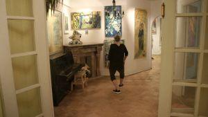 En svartklädd person dansar i en stor bostad med färgranna målningar på väggarna